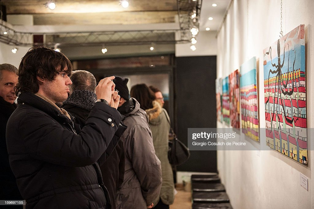 Visitors attend the opening of the exhibition of the paintings of the Mafia turncoat Gaspare Mutolo at Baccina 66 on January 18, 2013 in Rome, Italy.