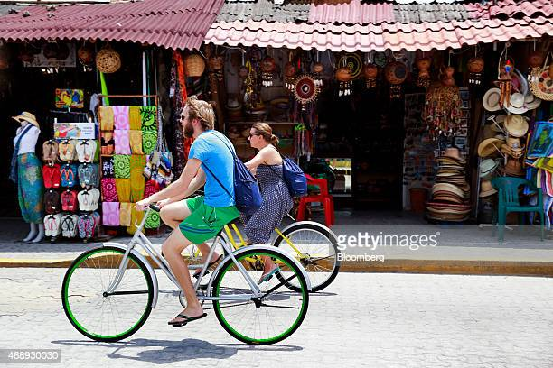 Visitors bike past shops in downtown Tulum Mexico on Friday April 3 2015 International tourists exceeded 142 million in 2014 while visitors increased...