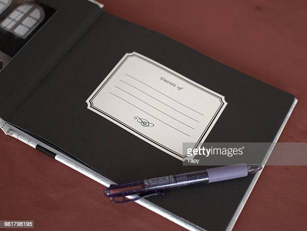 Visitors book and pen on table
