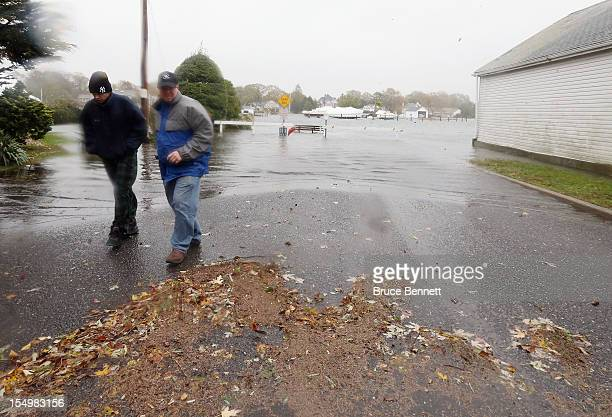 Visitors brave the elements brought in by Hurricane Sandy on a partially submerged Coles Avenue as high tide and winds flood the streets on October...