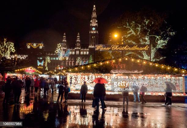 Visitors brave the rain as they visit a Christmas market outside City Hall in Vienna Austria on November 26 2018