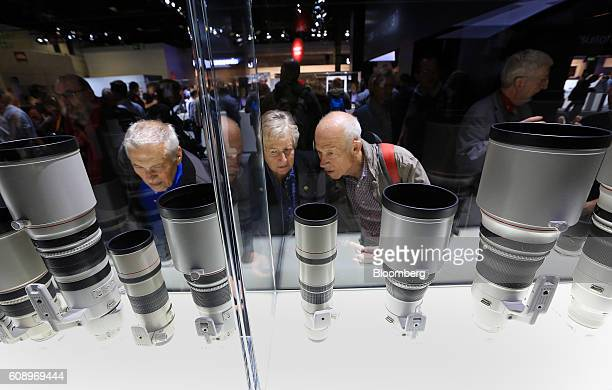 Visitors browse a display case containing a selection of Canon telephoto lenses manufactured by Canon Inc during the Photokina photography trade fair...