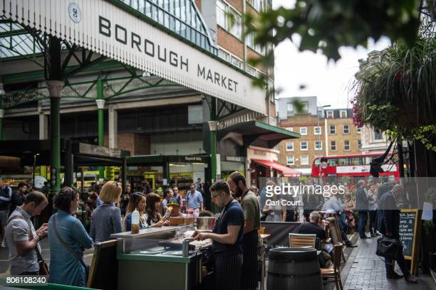 Visitors browse and buy food from stalls in Borough Market on July 3 2017 in London England On 3 June 2017 Islamist terrorists attacked people with...