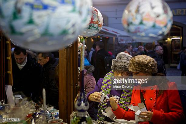 Visitors browse christmas decorations at the Christmas market at the Old Town Square on December 1 2013 in Prague Czech Republic Christmas markets...
