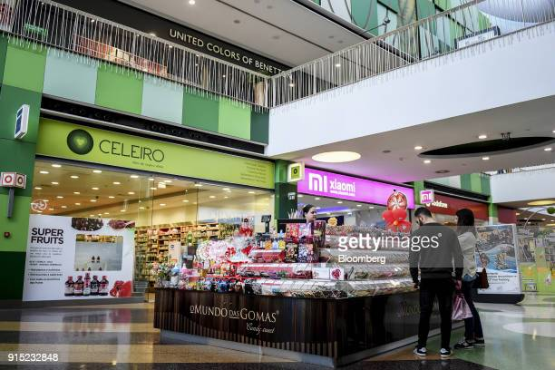 Visitors browse confectionary on display at a candy kiosk in a shopping arcade at the Dolce Vita Tejo shopping mall operated by AXA Real Estate...