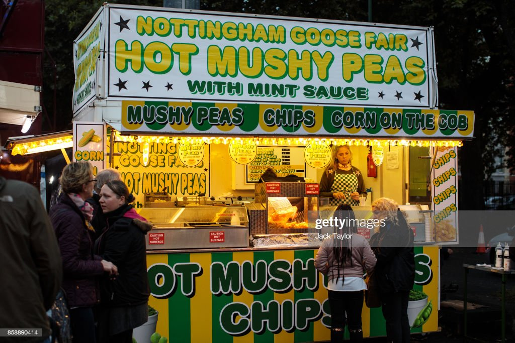 Visitors buy food from a mushy peas stall at the Nottingham Goose Fair in the Forest Recreation Ground on October 7, 2017 in Nottingham, England. The annual goose fair hosts over 500 attractions for thrill seekers including fun fair classics such as bumper cars, carousels and helter-skelters. The fair is thought to be over 700 years old and its name comes from its origins as a market in the forest grounds where thousands of geese were sold each year.