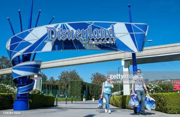 Visitors carrying Disney bags leave Disneyland on the day of the park's re-opening on April 30 in Anaheim, California, after it was closed in March...