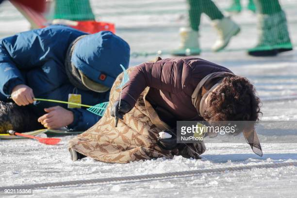 Visitors cast lines through holes drilled in the surface of a frozen river during a trout catching contest in Hwacheon South Korea on 6 January 2018...