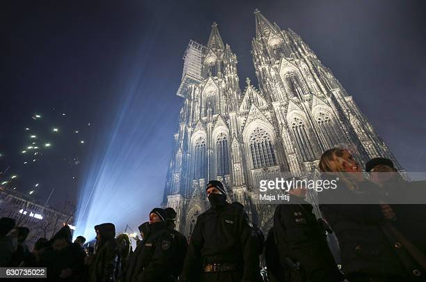 Visitors celebrate New Year's Eve as police stand guard in front of Cologne Cathedral not far from where on New Year's Eve one year ago hundreds of...