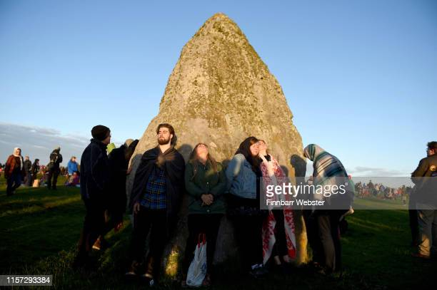 Visitors celebrate summer solstice and the dawn of the longest day of the year at Stonehenge on June 21 2019 in Amesbury England Visitors and modern...