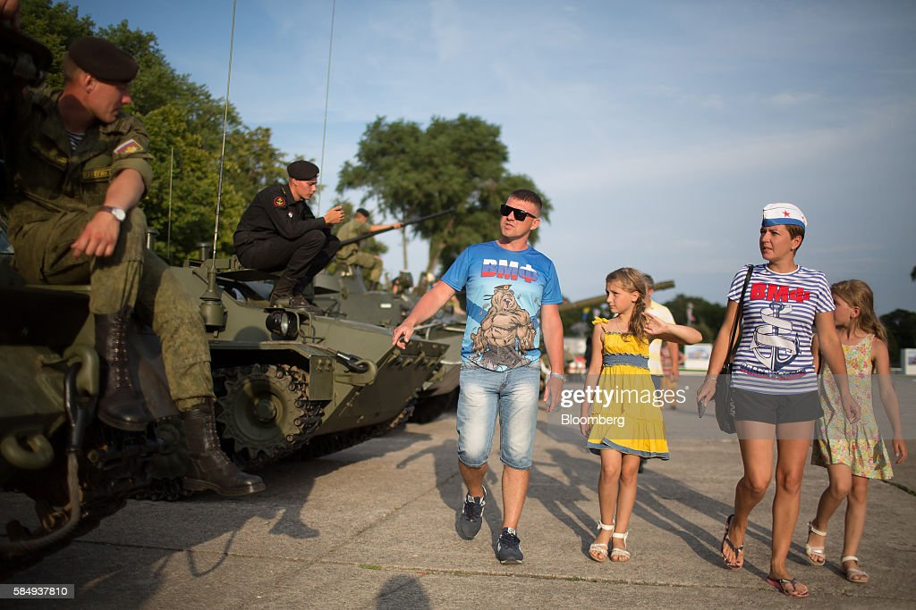 Visitors celebrating Russian Navy day walk past a display of Russian army military hardware at the Vistula lagoon in Baltiysk, Russia, on Sunday, July 31, 2016. Amid Russia's recent rearmament, the Kaliningrad region has increasingly returned to its Soviet-era role as a garrison on the strategic Baltic Sea coast. Photographer: Andrey Rudakov/Bloomberg via Getty Images