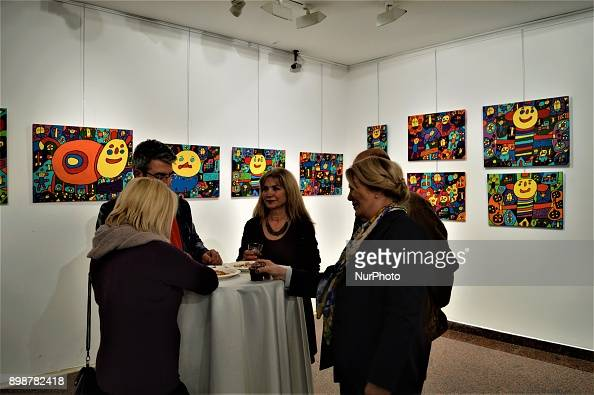 Visitors chat near paintings by Turkish painter Muhammed Yalcin, who