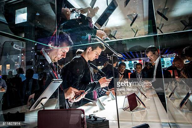 Visitors check HTC mobile phones on the second day of the event at the Fira Gran Via Complex on day 2 of the Mobile World Congress on February 23...