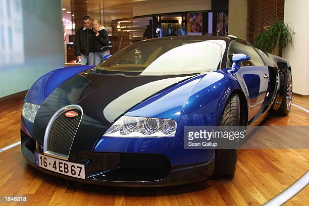 Visitors check out a Bugatti 164 Pierre Veyron car at a Bugatti showroom March 13 2003 in Berlin Germany German carmaker Volkswagen bought the...