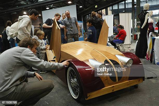 Visitors check out a DIY pedalpowered wooden car at the 2016 Berlin Maker Faire on October 1 2016 in Berlin Germany The Maker Faire combines a trade...