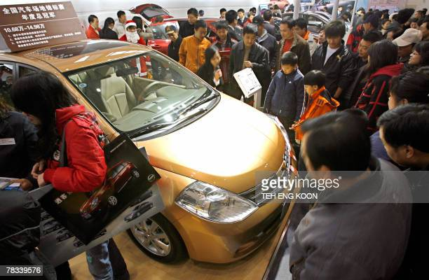 Visitors check out a latest car during the Beijing Auto Show in Beijing, 09 December 2007. Sales of passenger vehicles in China, the world's second...