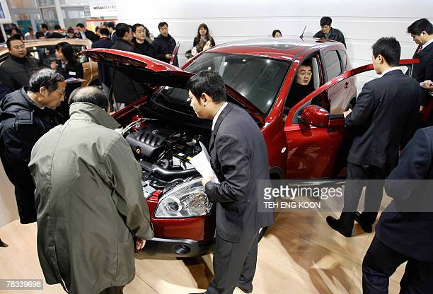 Visitors check out a new Nissan luxury car leaflet during the Beijing Auto Show in Beijing, 09 December 2007. Sales of passenger vehicles in China,...