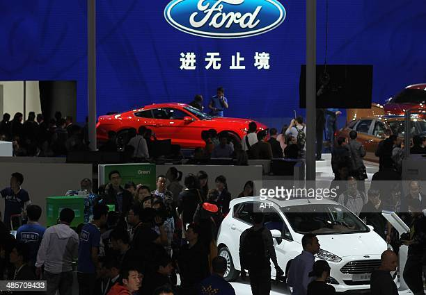 Visitors check out Ford cars on display at the China International Exhibition Center new venue during the 'Auto China 2014' Beijing International...