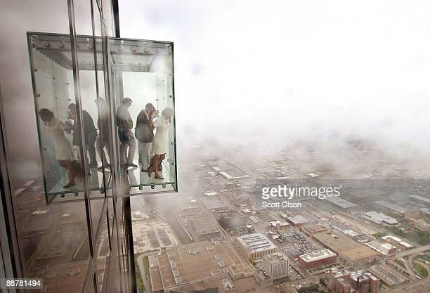 Visitors check out the view from the Ledge a new glass cube that juts out from the 103rd floor Skydeck of the Sears Tower during a media preview July...
