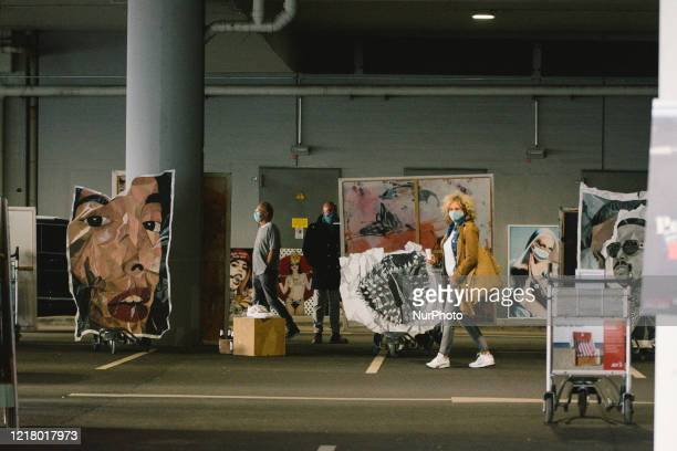 visitors check the art during the opening of drive in Gallery's show Nachtbroetchen 20 at Cologne airport parking lot amid the coronavirus crisis on...