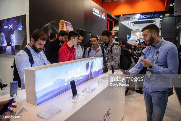 Visitors checks devices at Nubia booth on day 2 of the GSMA Mobile World Congress 2019 on February 26 2019 in Barcelona Spain The annual Mobile World...
