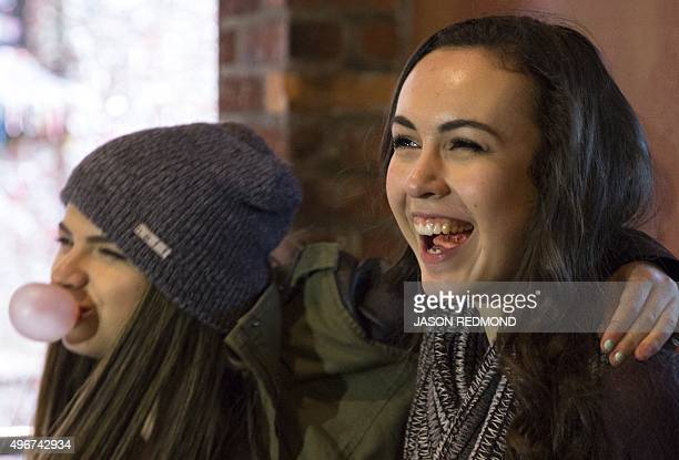 Visitors chew gum and pose for photos near the gum wall in Post Alley at the Pike Place Market in Seattle Washington on November 11 2015 A gumcovered...