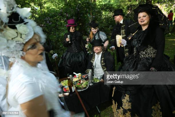 Visitors clad in Victorianinspired outfits relax at their banquet as they attend the Victorian Picnic on the first day of the annual WaveGotikTreffen...