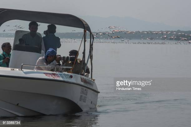 Visitors click picture of flamingos and other birds during the first boat ride of Flamingo Sanctuary inside Thane Creek on February 1 2018 in Mumbai...