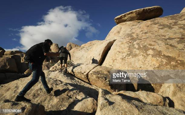 Visitors climb a rock formation in Joshua Tree National Park one day after the park reopened after being closed for two months due to the coronavirus...
