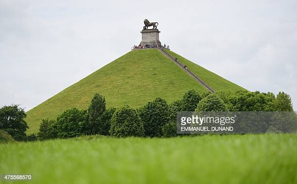 Visitors climb La Butte du Lion , the main memorial monument of the Battle of Waterloo, in front on a field where the 1815 Battle of Waterloo occured...