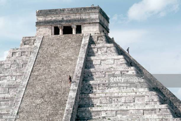 Visitors climb the steep staircase leading to the temple at the top of El Castillo or Pyrimid of Kukulkan at Chichen Itza Yucatan Mexico