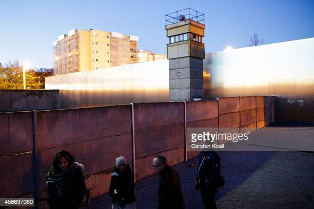 Visitors come to look out into the former 'death strip' between layers of the former Berlin Wall next to a former East German guard tower at the...