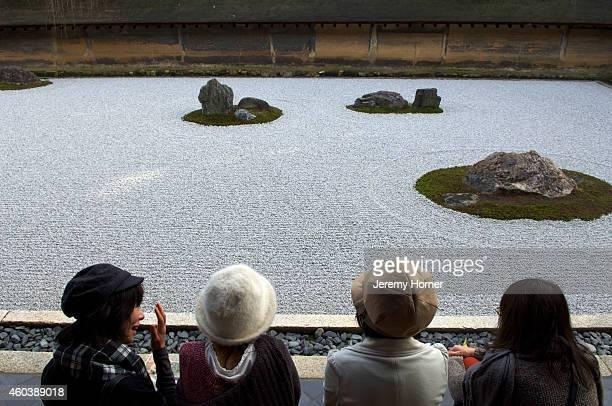 Visitors contemplate the Zen gardens of Ryoan Ji in Kyoto.