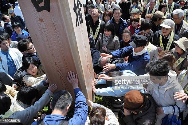 Visitors converge on the Ekobashira pillar that is connected by a gold rope to a statue within the main hall at Zenkoji Temple on April 9 2015 in...