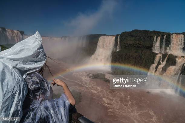 Visitors (mother and daughter), covered in plastic clothing but still drenched in spray, viewing from a walkway the Garganta del Diablo (Devil's Throat), Iguazu Falls (UNESCO World Heritage Site) from Brazilian side, Iguazu , Brazil