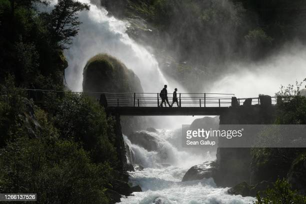 Visitors cross a bridge next to water rushing down a waterfall from the nearby melting Briksdal glacier on August 11, 2020 near Olden, Norway. The...