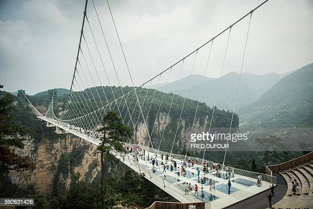 Visitors cross the world's highest and longest glassbottomed bridge above a valley in Zhangjiajie in China's Hunan Province on August 21 2016 / AFP /...