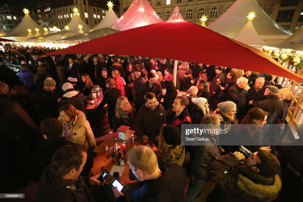 Visitors crowd a mulled wine stand at the annual Christmas market at Gendarmenmarkt on its opening day on November 26, 2012 in Berlin, Germany. Christmas markets, with their stalls selling mulled wine (Gluehwein), Christmas tree decorations and other delights, are an integral part of German Christmas tradition, and many of them opened across Germany today.