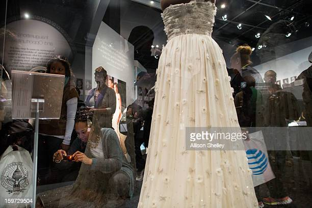 Visitors crowd around a display featuring the dress worn by Michelle Obama on inauguration day 2009 at an exhibition entitled The First Ladies at the...