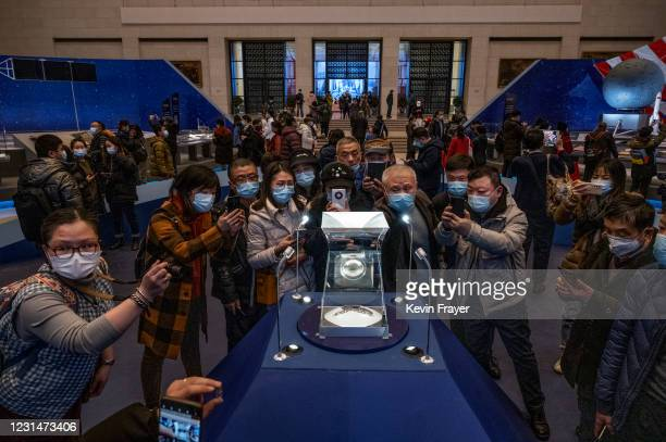 Visitors crowd as they look and take pictures of a case holding lunar rock and debris recently collected from the Moon by China's space program that...