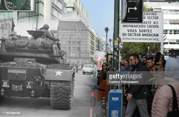 Visitors crowd Checkpoint Charlie, where the American Zone of occupation met East Berlin during the Cold War, on October 23, 2019 in Berlin, Germany....