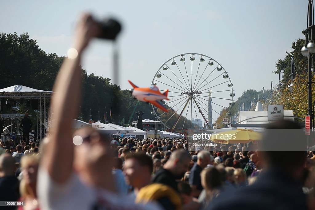 Visitors crowd Strasse des 17. Juni in Tiergarten Park as a ferris wheel spins on German Unity Day (Tag der Deutschen Einheit) on October 3, 2014 in Berlin, Germany. Germany is celebrating the 24th anniversary of the day when former West Germany and East Germany reunited into modern Germany in 1990 following the end of the Cold War. This year Germany will also celebrate the 25th anniversary of the fall of the Berlin Wall that heralded the collapse of communist authority in East Germany.