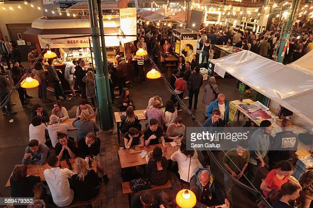 Visitors crowd the Markthalle Neun indoor market hall among food stalls during weekly Street Food Thursday on July 14 2016 in Berlin Germany While...