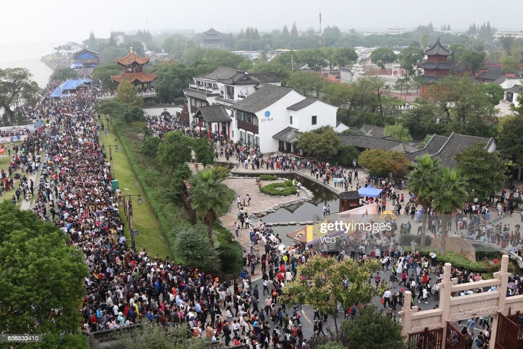 Visitors crowd to watch the soaring tide of the Qiantang River at Yanguan Ancient Town on October 6, 2017 in Jiaxing, Zhejiang Province of China. When the surging tide comes, around 110,000 visitors flock there to watch it.