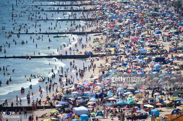 Visitors crowd together as they enjoy the hot weather on the beach on June 25, 2020 in Bournemouth, United Kingdom. The UK is experiencing a summer...