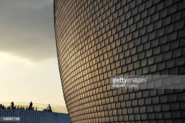 Visitors cycling on the top of the Norvegian pavilion are dwarfed by the Finnish pavilion as the sun sets over the site of the World Expo 2010 in...