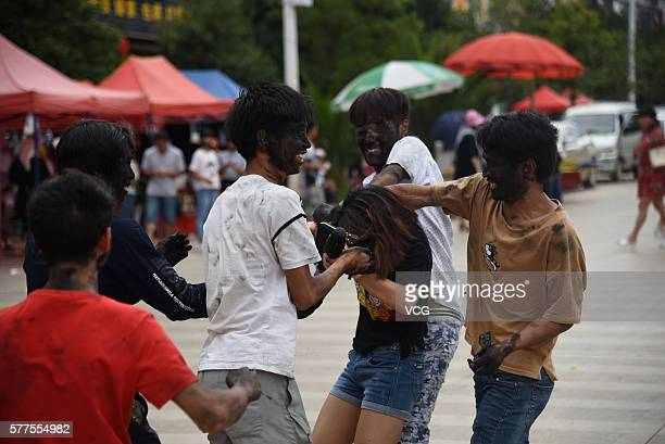 Visitors daub rice ash onto a girl's face during the Face Painting Festival in Puzhehei Resort of Qiubei County on July 18 2016 in Wenshan Prefecture...
