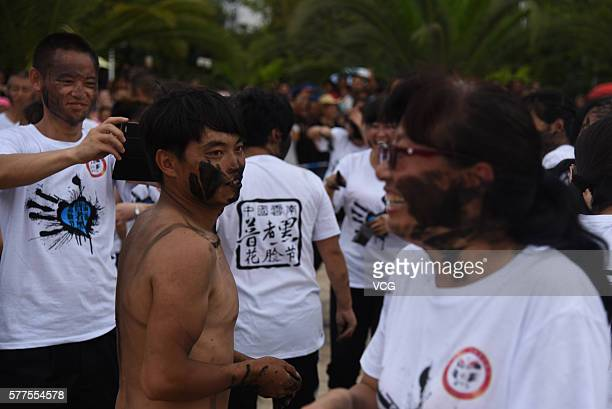 Visitors daub rice ash onto each other during the Face Painting Festival in Puzhehei Resort of Qiubei County on July 18, 2016 in Wenshan Prefecture,...