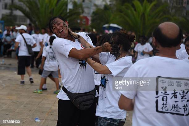 Visitors daub rice ash onto each other during the Face Painting Festival in Puzhehei Resort of Qiubei County on July 18 2016 in Wenshan Prefecture...