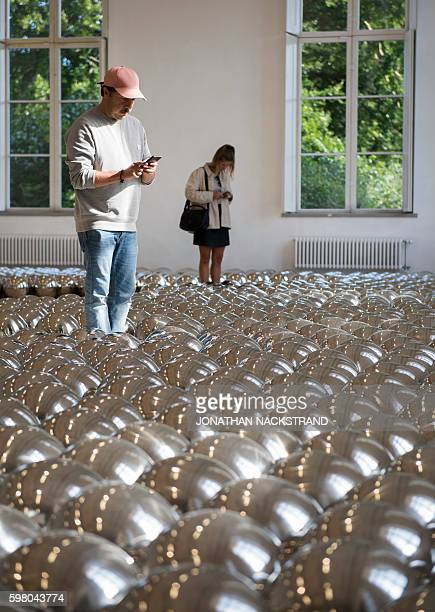 Visitors discover an art installation entitled 'Dots Obsession' by Japanese artist Yayoi Kusama part of the In Infinity art exhibition presented at...